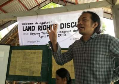 Public interest lawyer Karl Carumba discussing land rights cases with farmers and indigenous peoples.