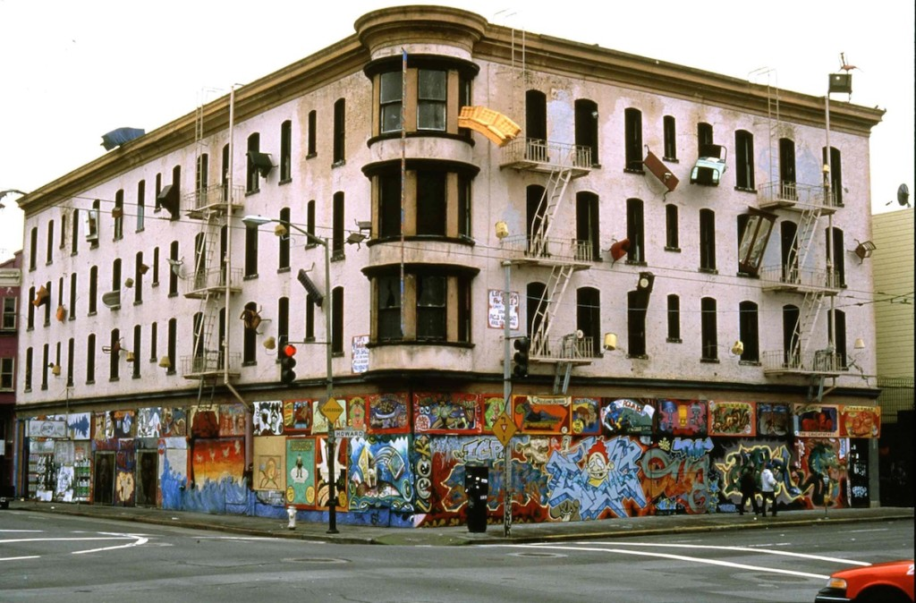 Defenestration. Against society's expectations, these everyday objects flood out of windows like escapees, out onto available ledges, up and down the walls, onto the fire escapes and off the roof. San Francisco, California. 1997. Multi-disciplinary sculptural mural by Brian Goggin.